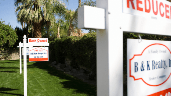 "Lawn with ""just reduced"" real estate sign in front of home"
