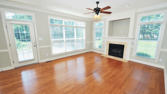 Interior shot of empty living room with hardwood floors, ceiling fan, and fireplace